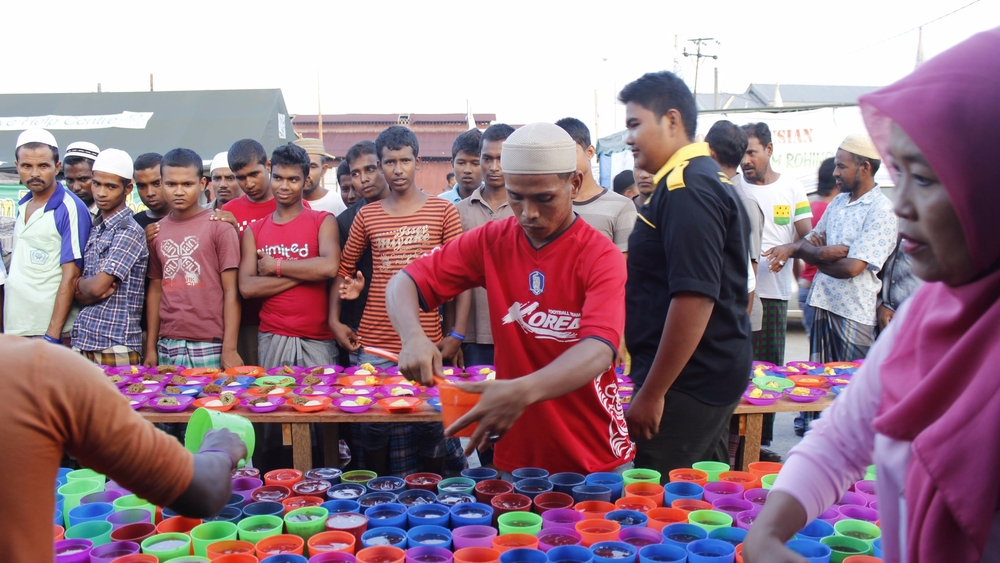"Acehnese fisherman, Karim, who was involved in the rescue of hundreds of Rohingya and Bangladeshi ""boat people"" in May, serves 'iftar' juice for the breaking of fast during the month of Ramadhan in the temporary refugee camp in Langsa, Aceh."