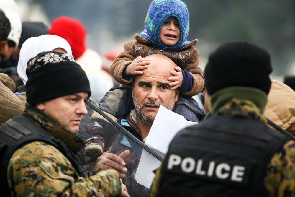 A man with a crying child shows his Greek registration paper to heavily armed Macedonian border police. Only Syrians, Afghans and Iraqis were allowed to cross the border.