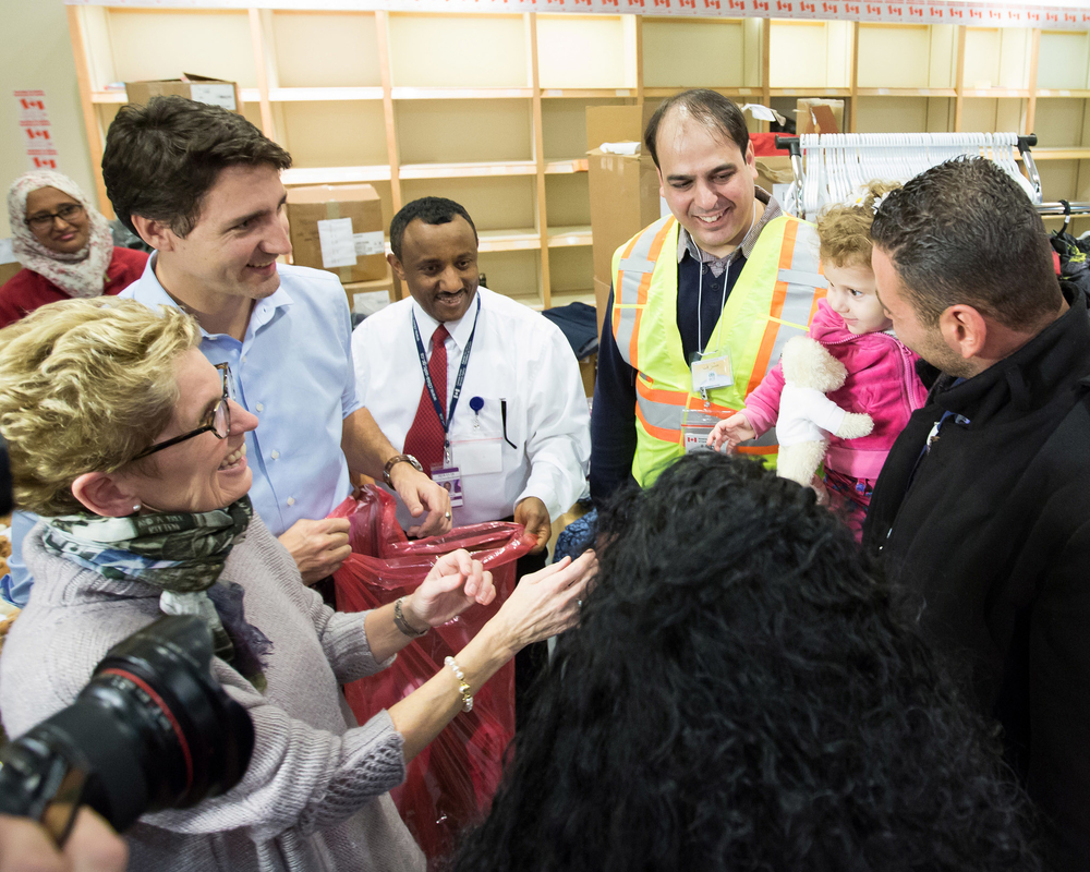 Canadian Prime Minister Justin Trudeau and Ontario Premier Kathleen Wynne welcome Syrian refugees Kevork Jamkossian and his daughter Madeleine who were among 163 Syrians to arrive in Canada on 10 December, the first of 10,000 expected before the end of 20
