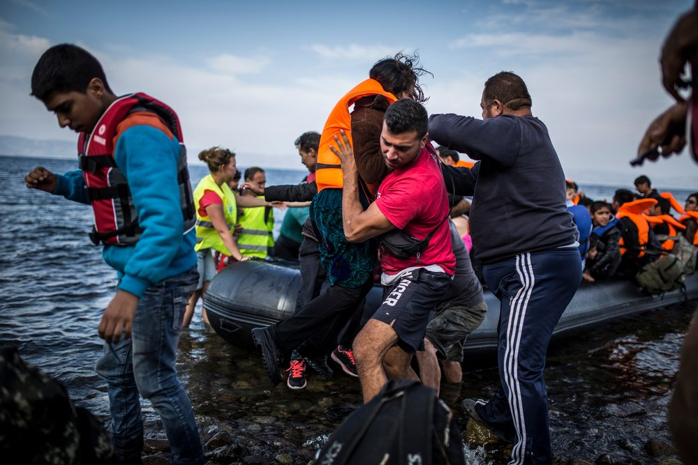 Salam Aldeen of volunteer group Team Humanity helps refugees disembark from a boat arriving on the Greek island of Lesvos