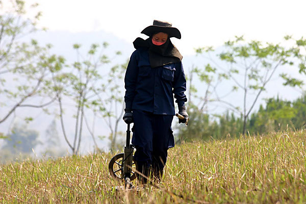 An employee of Mines Advistory Group searches for unexploded munitions in central Laos in August 2010