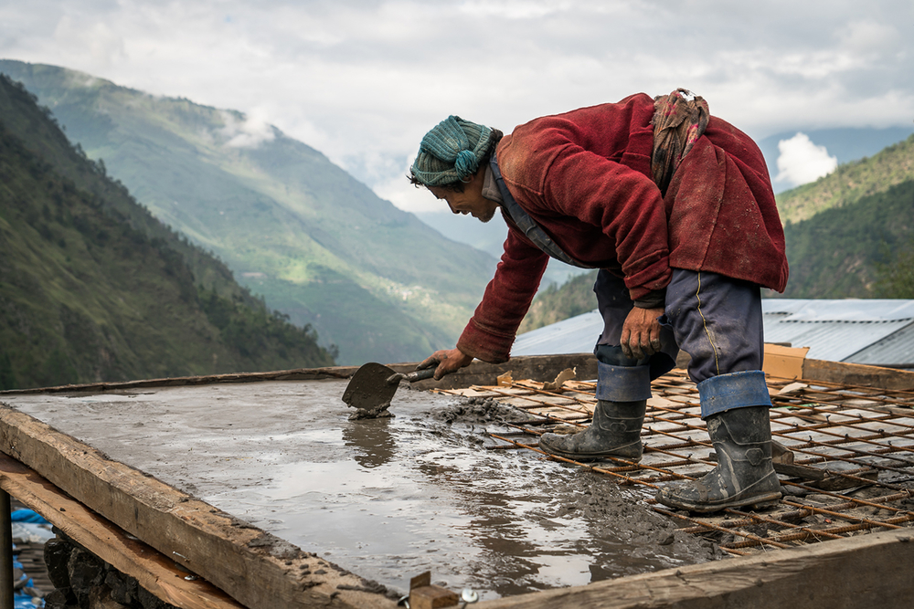 A Nepalese man in a red coat repairs a roof with mountains in the background