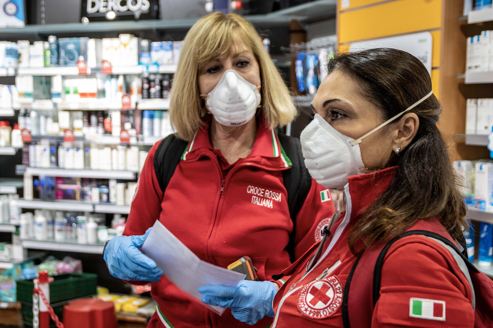 Italian Red Cross volunteers collect medicines at a pharmacy