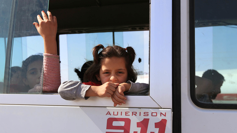 A Syrian child who fled violence with her family after the recent Turkish offensive is taken by bus to a displacement camp near Dohuk in northern Iraq.