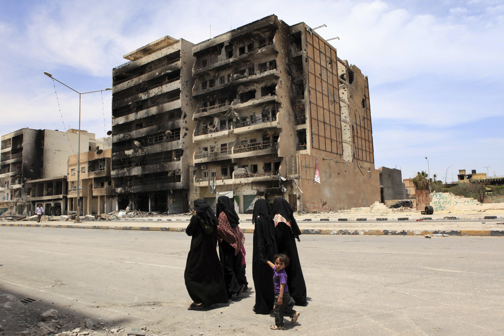 Women walking in front of bombed out buildings in Misrata