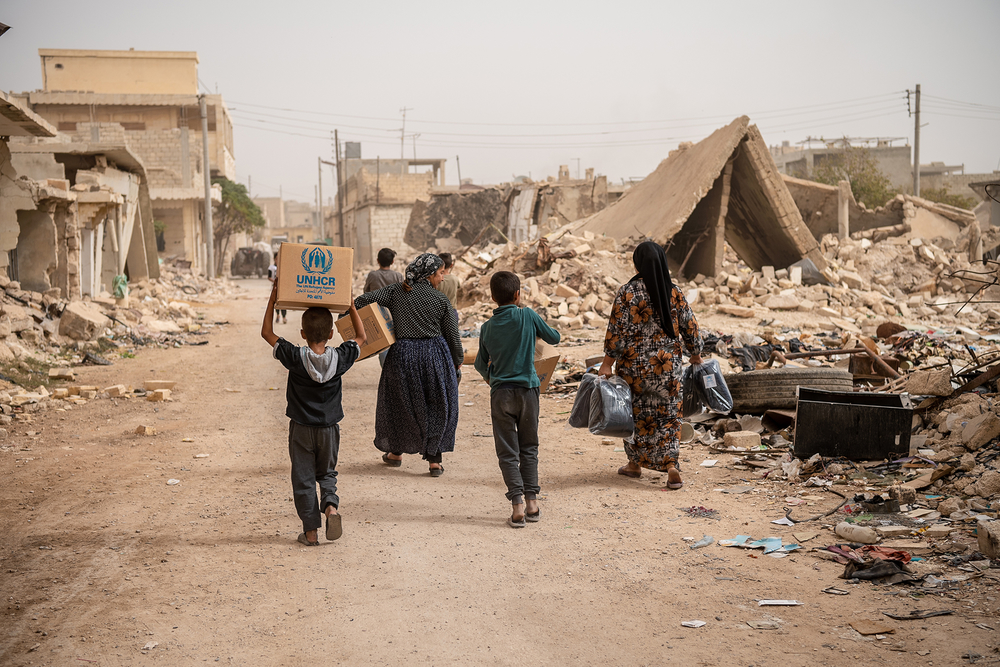 Internally displaced Syrians walk away through rubble with boxes of aid.