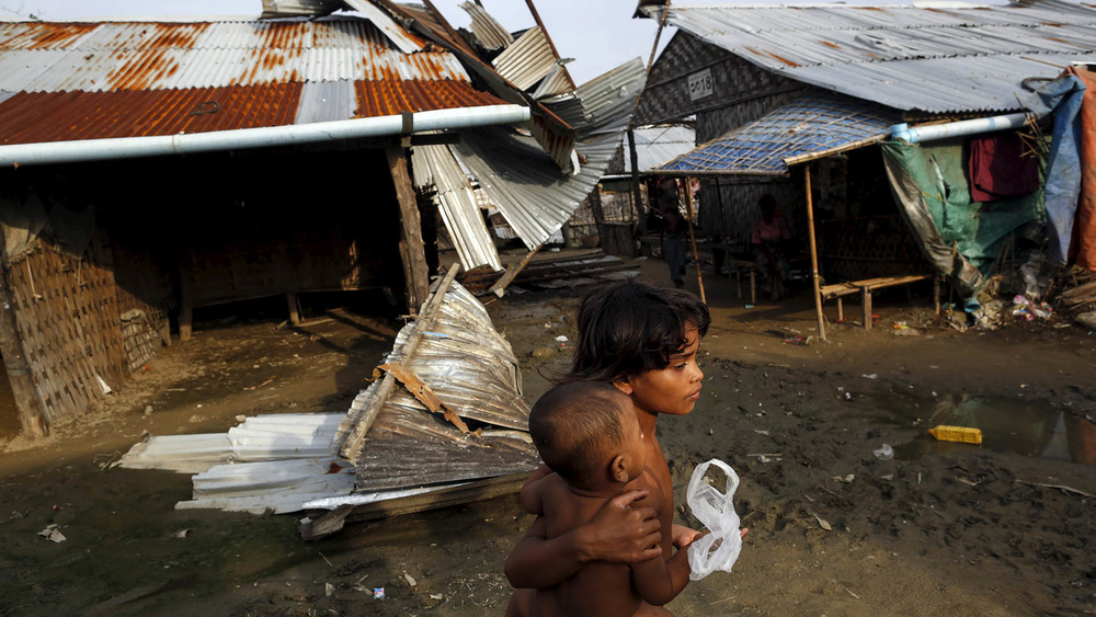Rohingya girls pass in front of a damaged shelter in a displacement camp outside Sittwe in Myanmar's Rakhine State in August 2015.