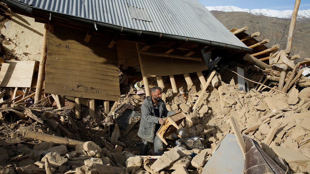 A man clears debris outside a house damaged in the earthquake in Cevrimtas.
