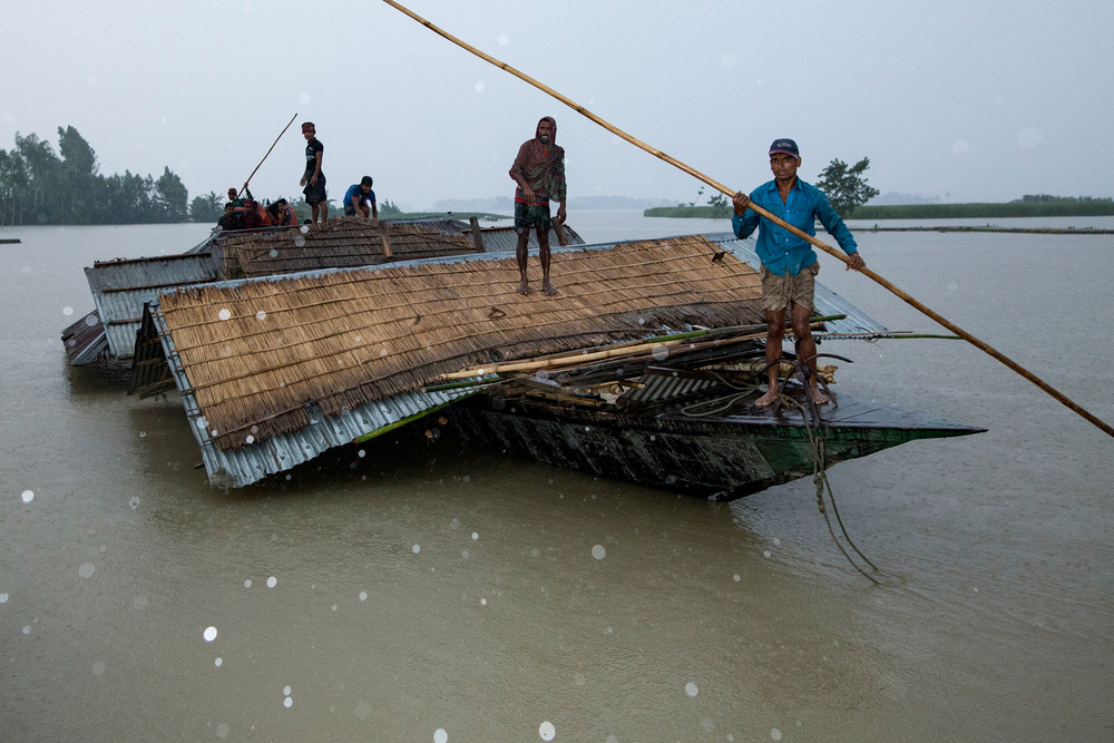 Photo of parts of homes on boats in flooded Bangladesh