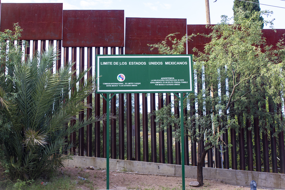 A metal border fence with a sign in Spanish warning of penalties.