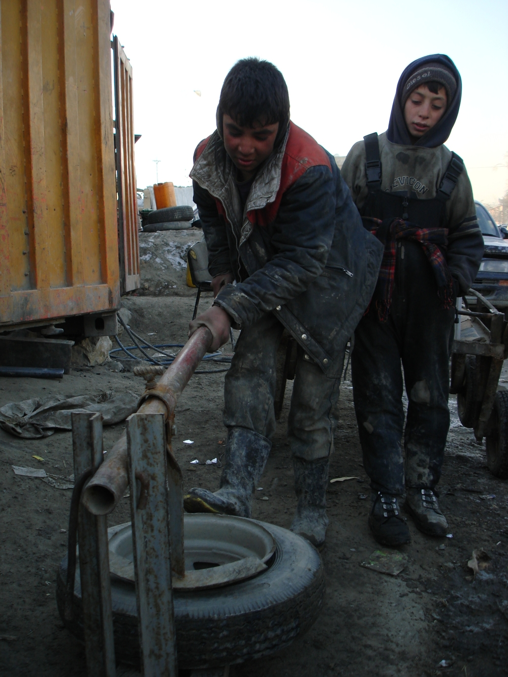 Sayed and his friend working in a tyre-repair shop in Kabul city
