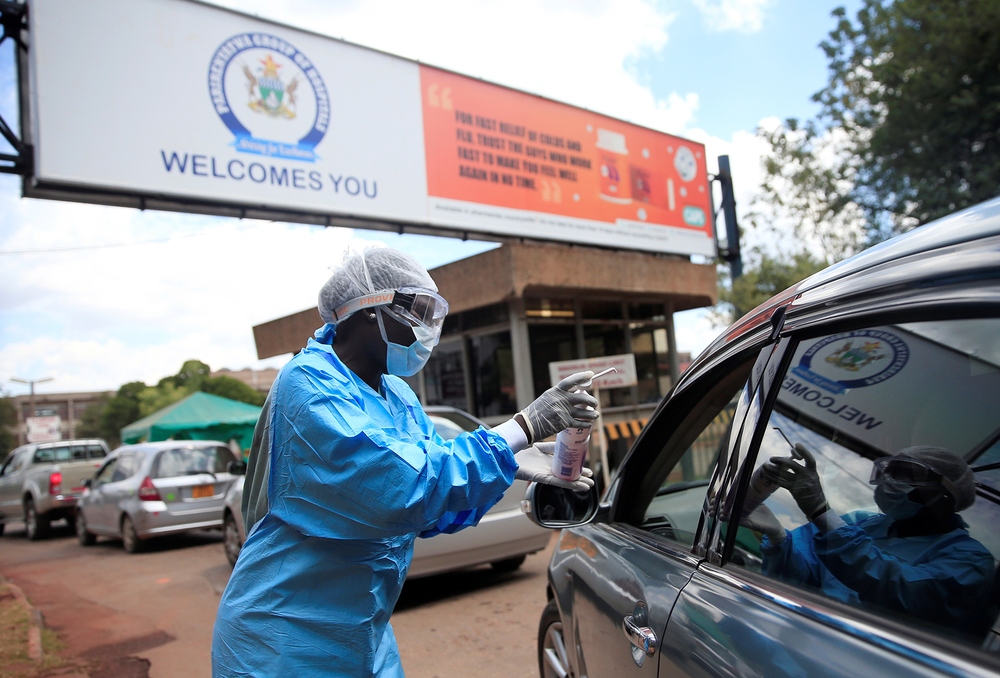 A health worker screens and sanitises visitors in Harare