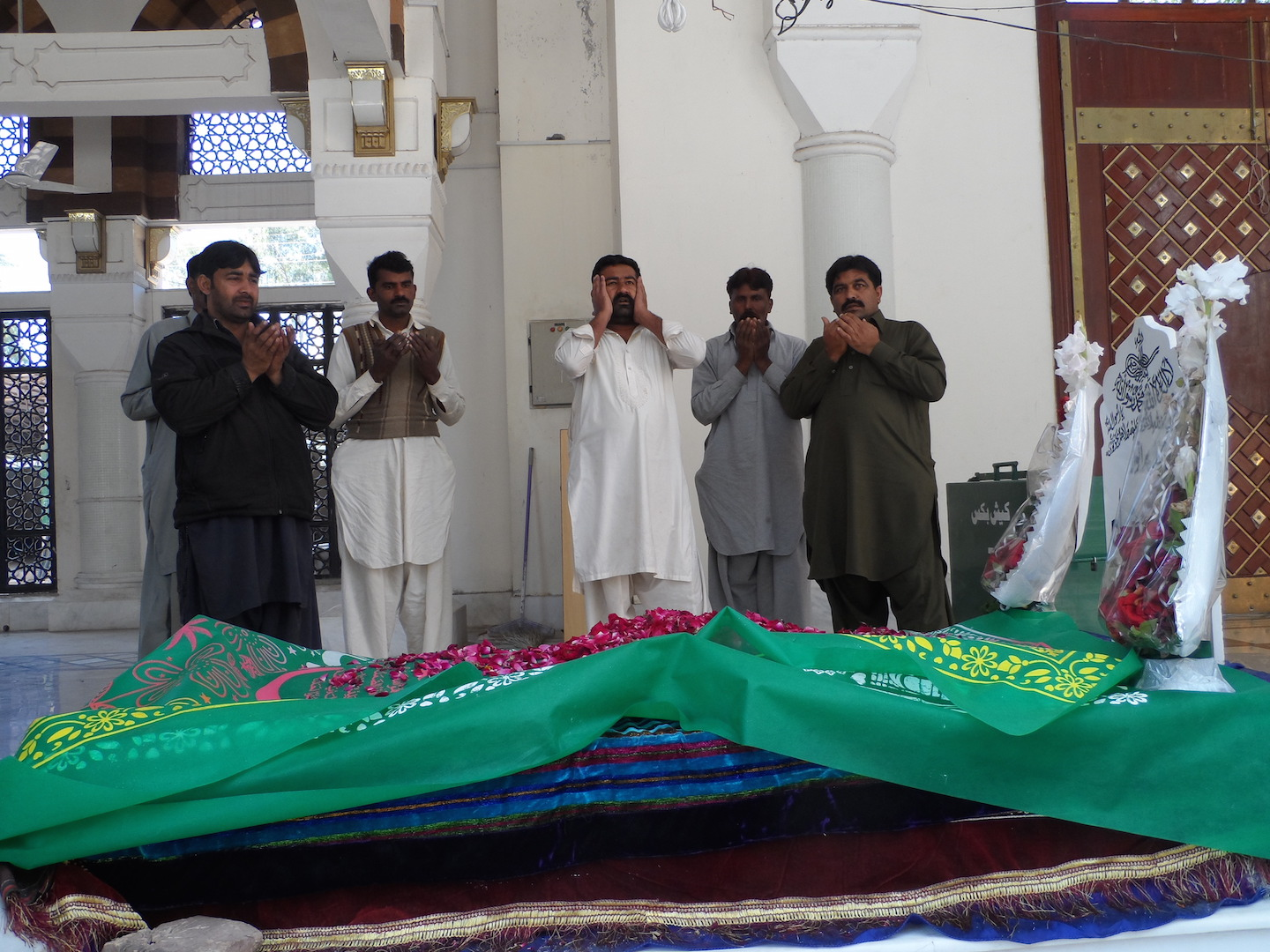 Devotees pray at the burial chamber in the Bari Imam Sufi shrine in Islamabad