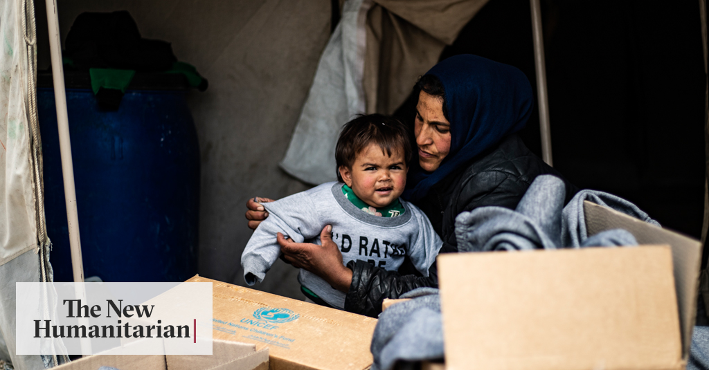 Mariam, who fled rural Aleppo two years ago with her husband and family, helps one of her six children try on new winter clothes delivered to Ain Issa camp, northeastern Syria.