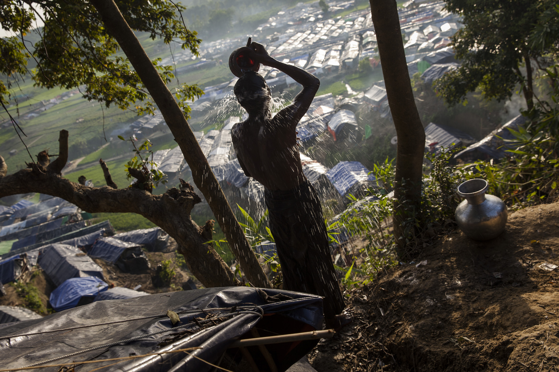 A Rohingya man washes himself on a hill overlooking tarpaulin-covered shelters