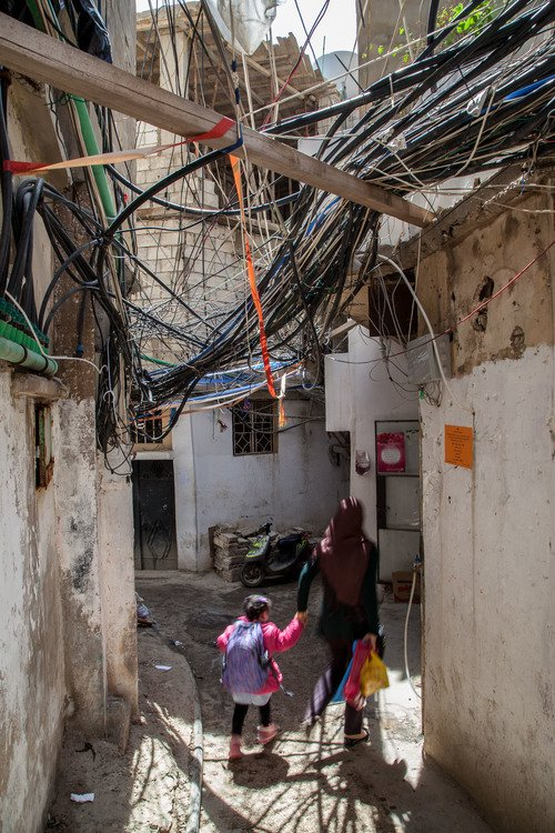 A woman and a child walk underneath many disorganized and loose wires.