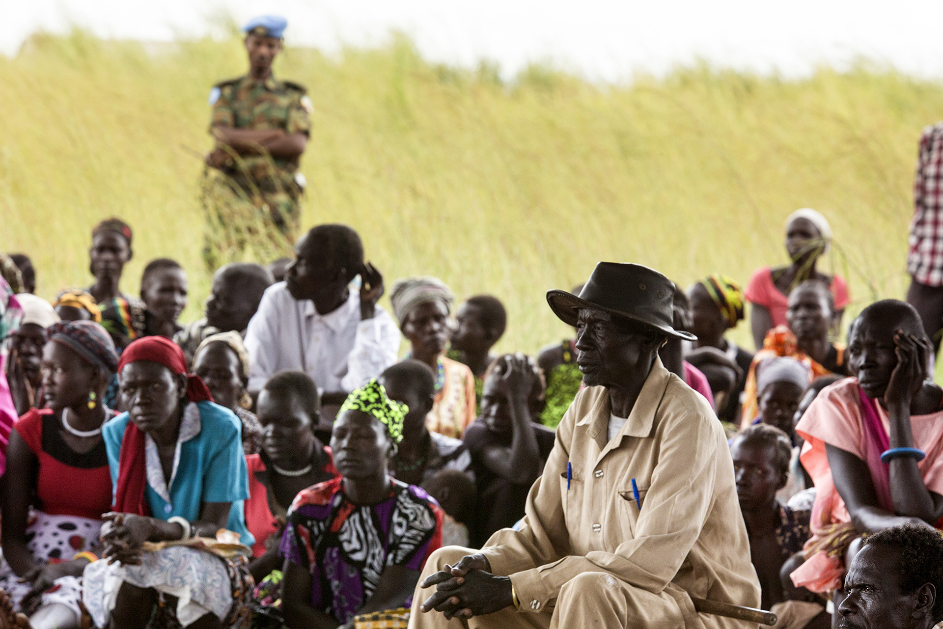 Photo of group of people with soldier in background in South Sudan.