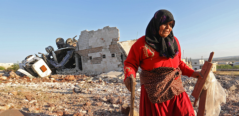 Photo of woman in Idlib near a destroyed building after air strike
