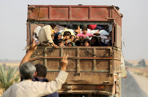 Kurdish Syrian civilians flee the town of Kobane on the Turkish border on 16 October 2019.