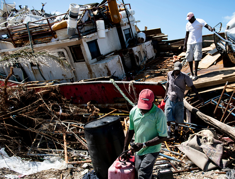 People recover items from a beached boat after Hurricane Dorian 5 September 2019, in Marsh Harbor, Great Abaco.