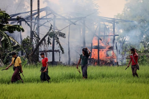 Unidentified men carry knives and slingshots as they walk past a burning house in Gawdu Tharya village near Maungdaw in Rakhine state in northern Myanmar on 7 September 2017.