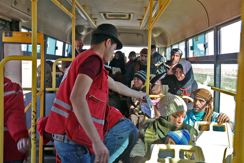 Photo of a Syrian Red Crescent member on a bus at the Jordanian border with displaced people from Rukban.