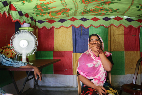 Photo of Romida Begum sitting inside with her hand covering her smiling mouth