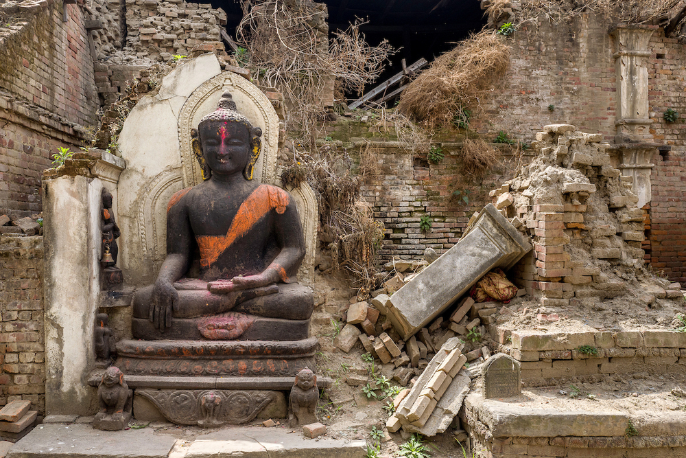 A statue of a smiling Buddha stands surrounded by debris and a house destroyed by the earthquake in Bhaktapur, Nepal