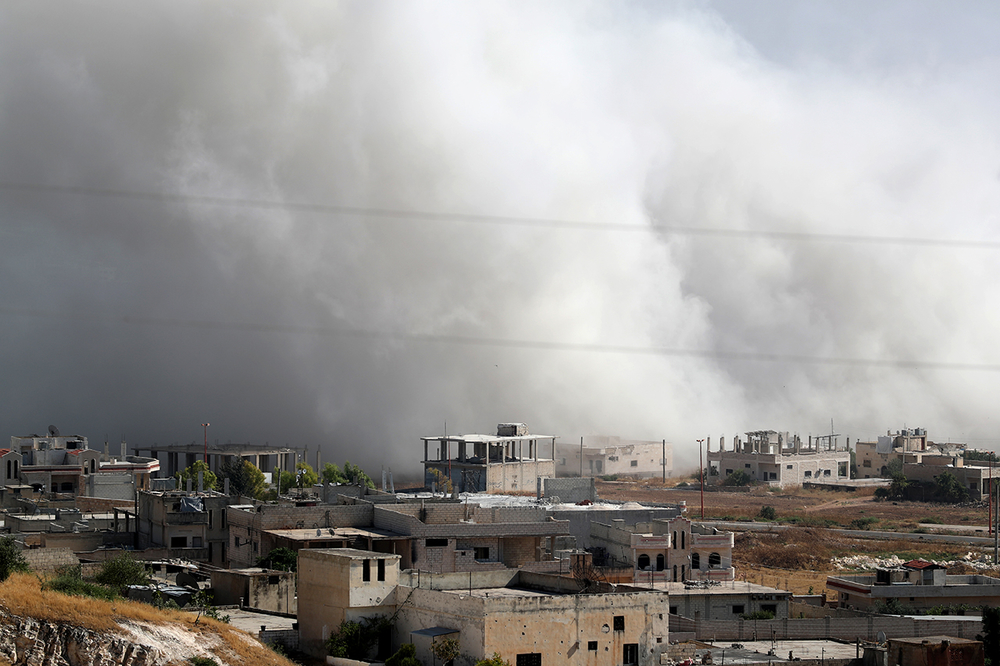 photo of smoke over buildings in idlib air strike in Syria