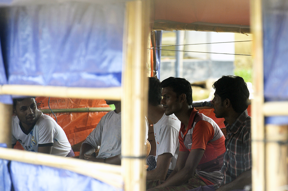 Photo of Rohingya men in a camp in Bangladesh, sitting inside a temporary structure