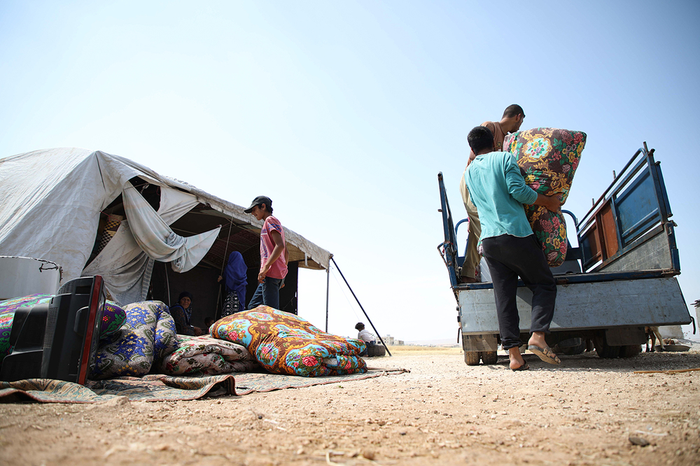 Displaced Syrian men pack their belongings to sell in the rebel-held western part of Aleppo province, 13 June 2019.
