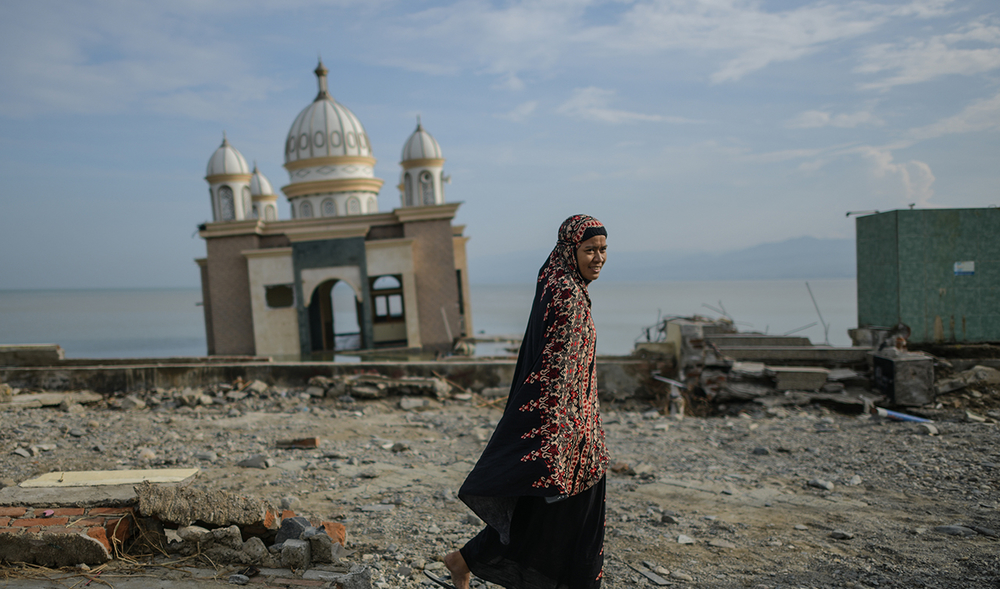 A tilted, damaged mosque in the background as a woman walks in front