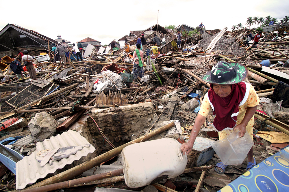 A woman in a hat is in the foreground amidst tsunami-damaged buildings.