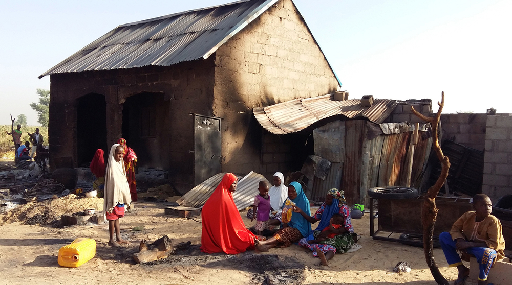 Women and children sit outside a burnt house after a suspected Boko Haram attack in Bulabulin village, in northeast Nigeria on 1 November 2018.
