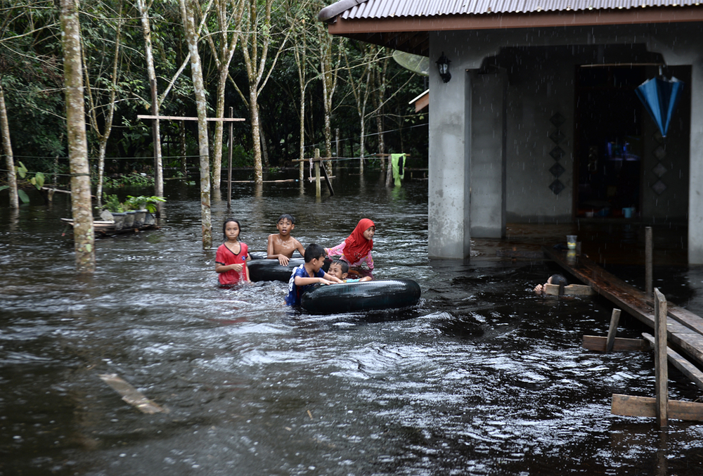 Children play outside a house affected by floodwaters following heavy rains in southern Thai province of Narathiwat on 2 December 2019.