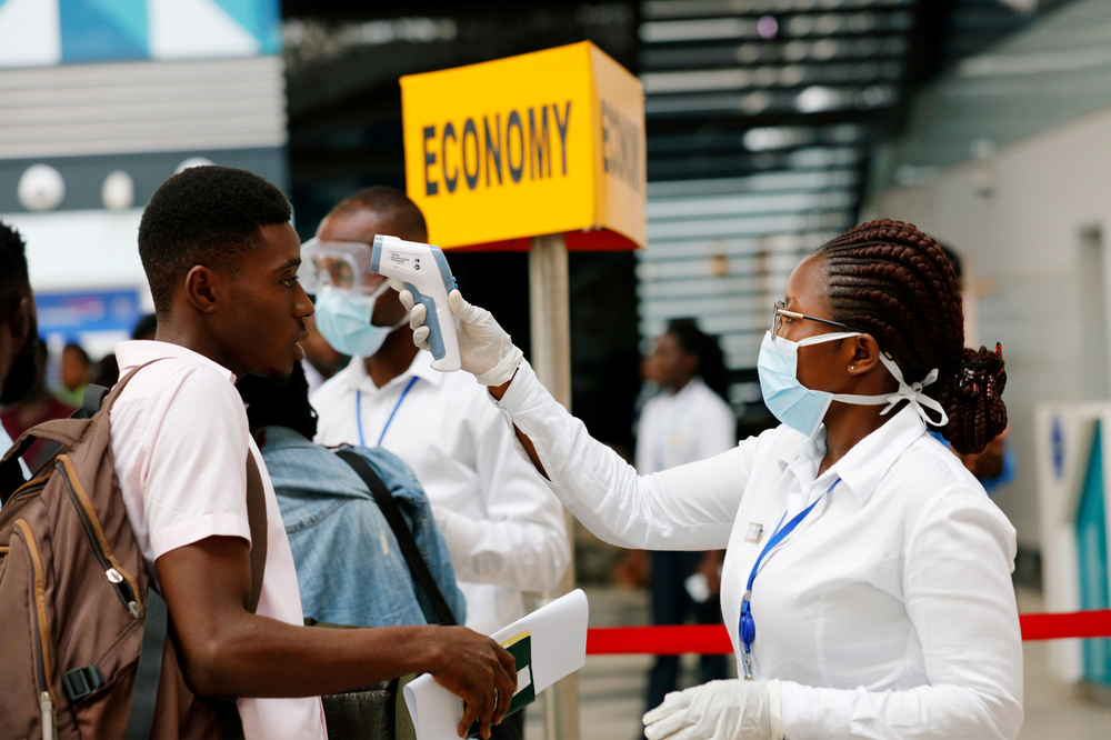 A health worker checks the temperature of a traveller in coronavirus screening at Kotoka International Airport, Accra, Ghana.