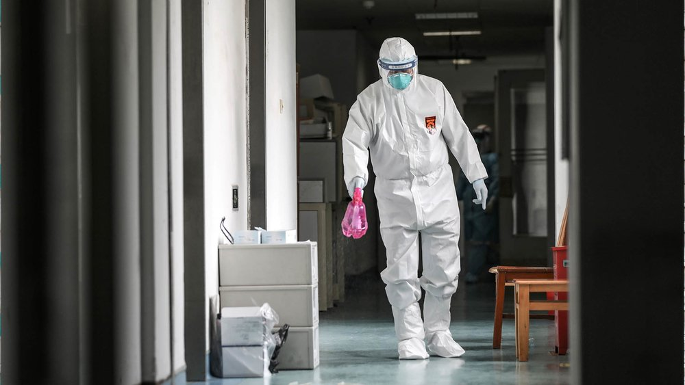 A medical worker wearing a protective suit disinfects the hallway at Jinyintan hospital in Wuhan.