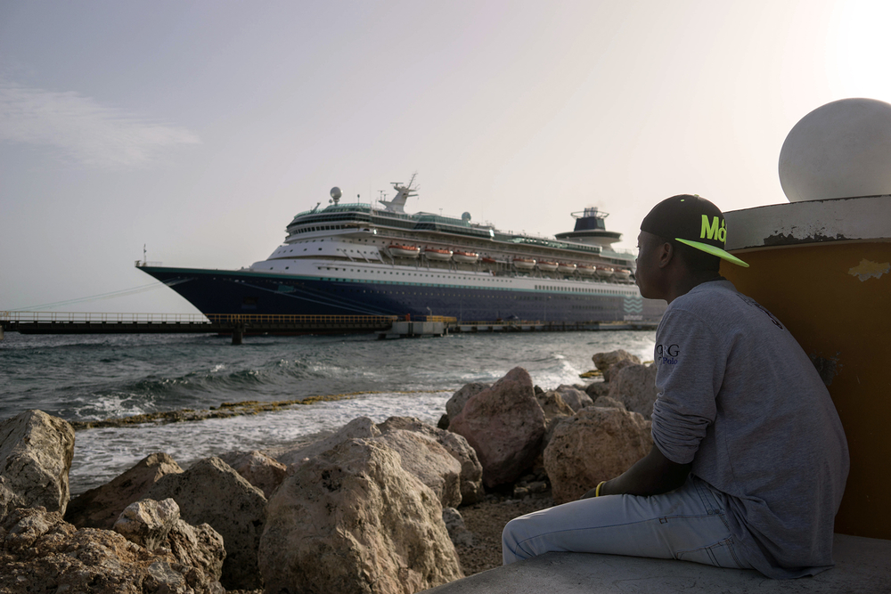 A man sits on the sea wall looking at a cruise ship