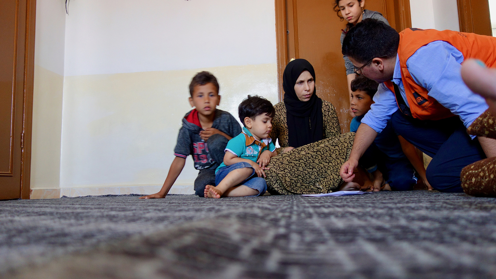 Photo of an aid worker from Jordan meeting a Syrian family
