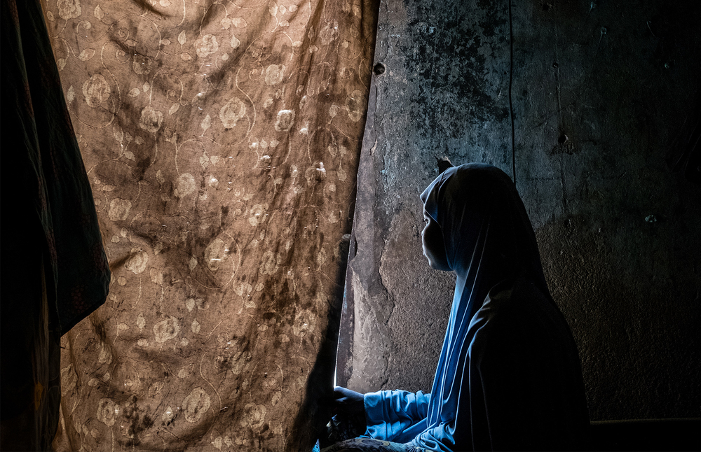 A girl who was kidnapped by Boko Haram but escaped looks out the window of a camp room in Maiduguri, Nigeria.