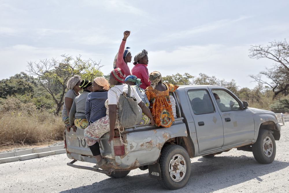 Women in the back of a lorry, one with her hand stretched to the sky, drive down a road in cameroon.