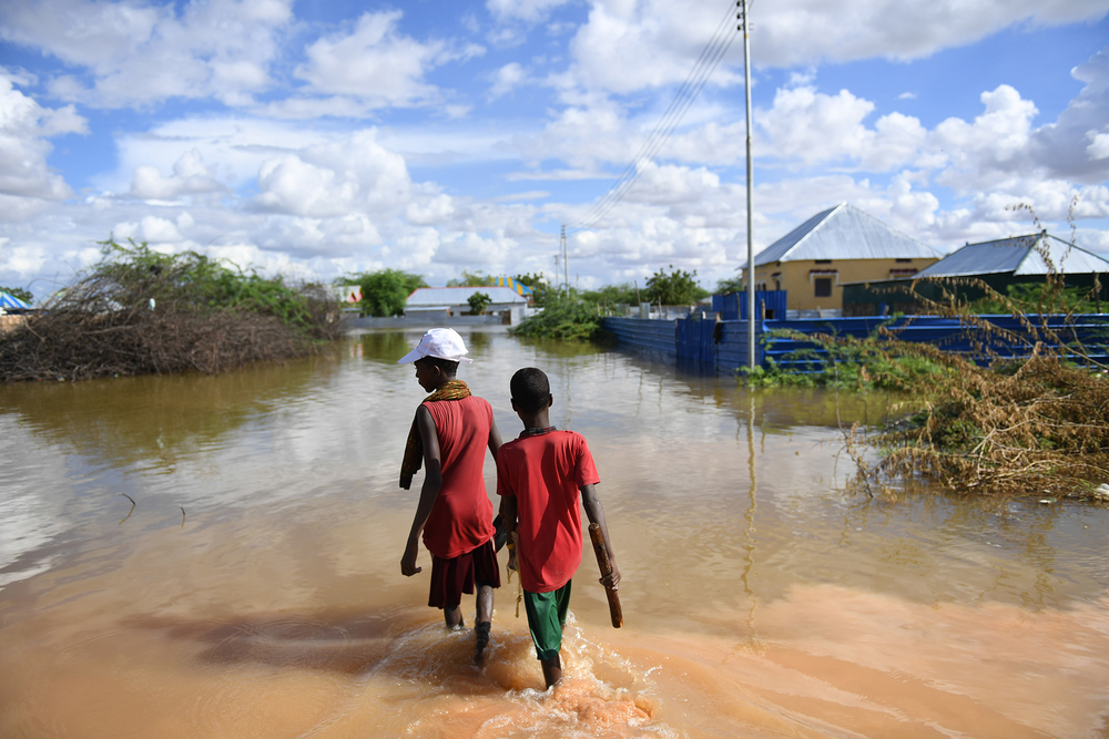 Young boys of Hawa-taako walk through a section of the flooded residential area in Belet Weyne, Somalia in 2018.