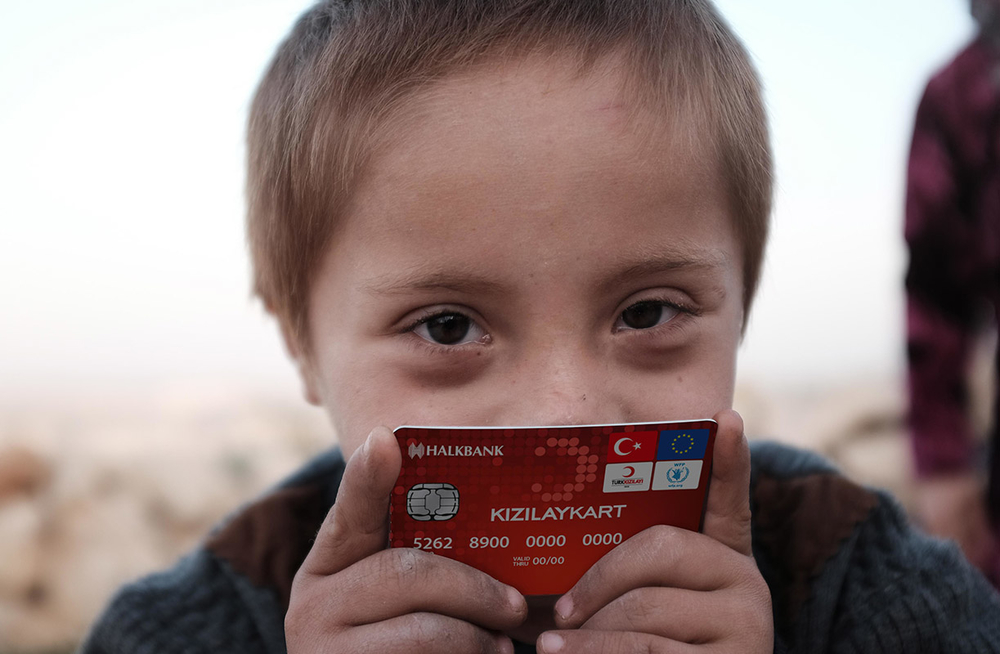 A refugee child holds a prototype bank card issued by the EU-funded Emergency Social Safety Net programme to provide money transfers to refugees in Turkey.
