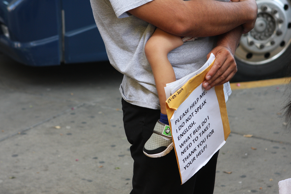 Photo of immigrant from Mexico into the US holding a sign.