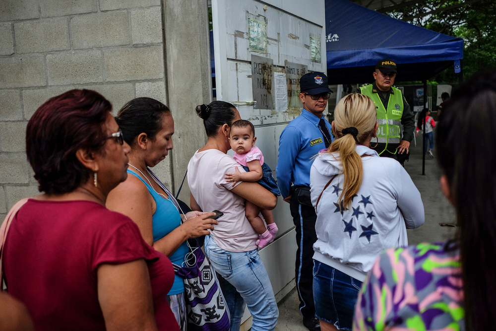 People lining up at the door of Prados del Este registration office in Cúcuta.