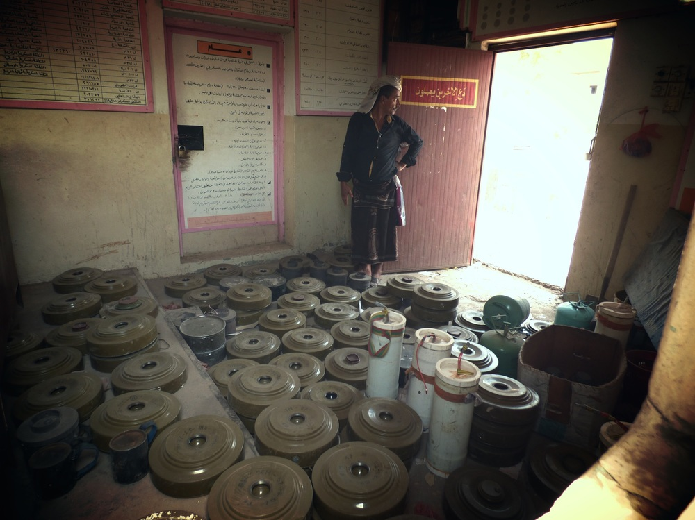 A person in Aden, Yemen stands in a room full of mines.