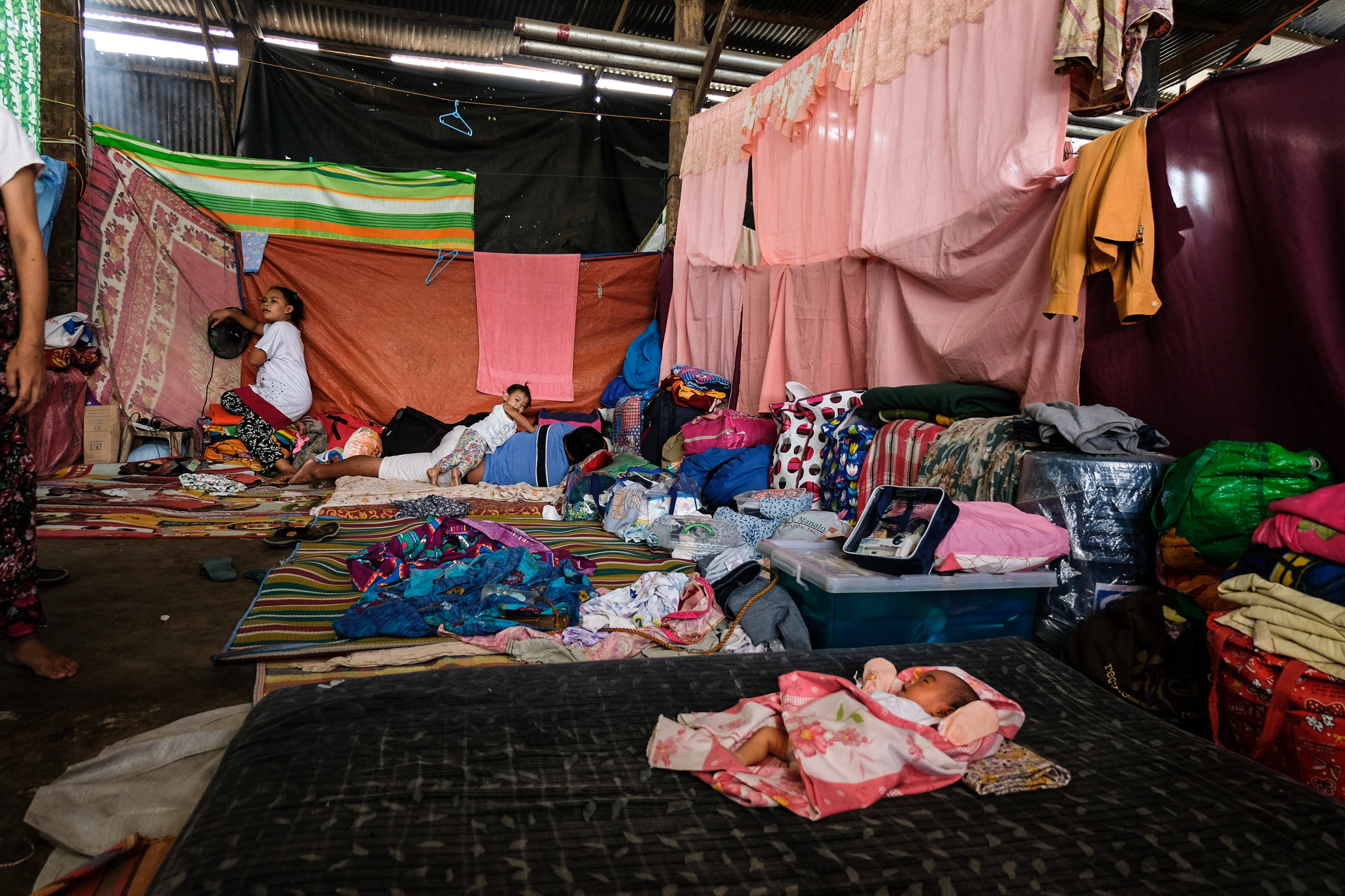 A baby lies on a mat in a warehouse where displaced Marawi residents have sought refuge.