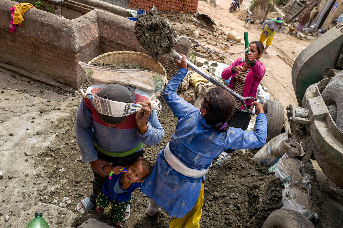 A construction worker takes care of his young daughter while two women load his basket with sand in Bhaktapur, Nepal.