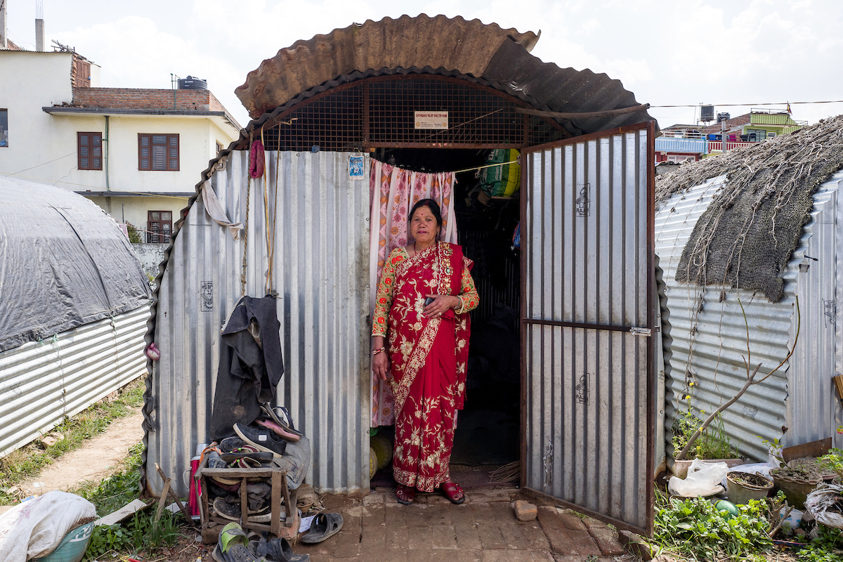 Hira Devi, 50, stands outside her temporary shelter in Harisiddhi, Nepal