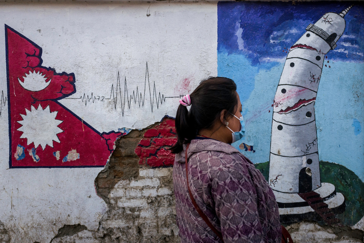 A woman passes in front of a painting representing the destruction of the Dharahara tower in Kathmandu, Nepal.